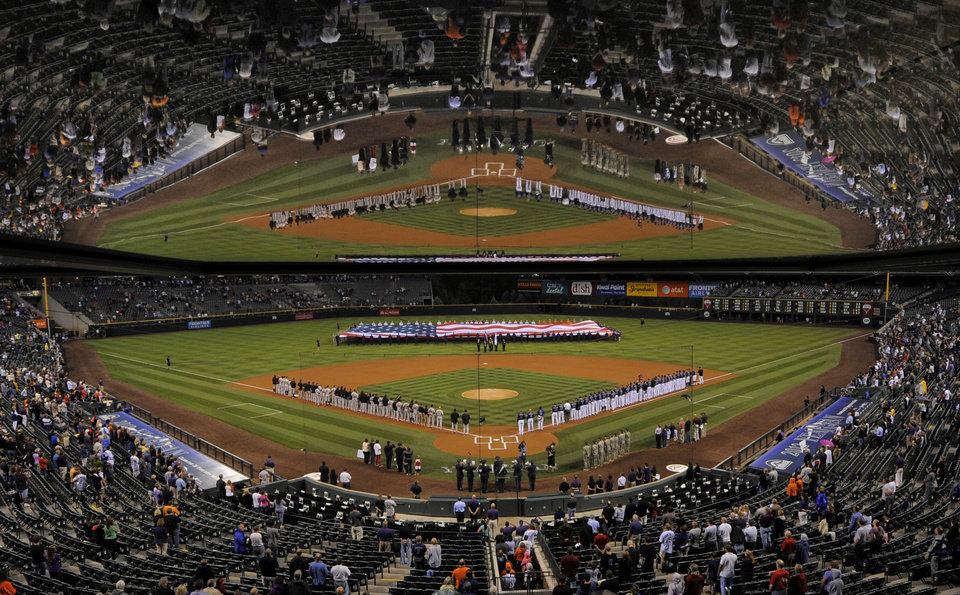 Photo -   The field is reflected as the San Francisco Giants and the Colorado Rockies line up to remember the 11th anniversary of the Sept. 11 terrorist attacks before their baseball game, Tuesday, Sept. 11, 2012, in Denver. (AP Photo/Jack Dempsey)
