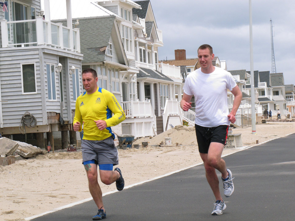 Photo - Joggers run past a house damaged by Superstorm Sandy on the Manasquan, N.J., beachfront, Saturday, May 25, 2013. Communities that were hard-hit by Superstorm Sandy, including Manasquan, are hoping for a profitable summer season to help them recover. (AP Photo/Wayne Parry)