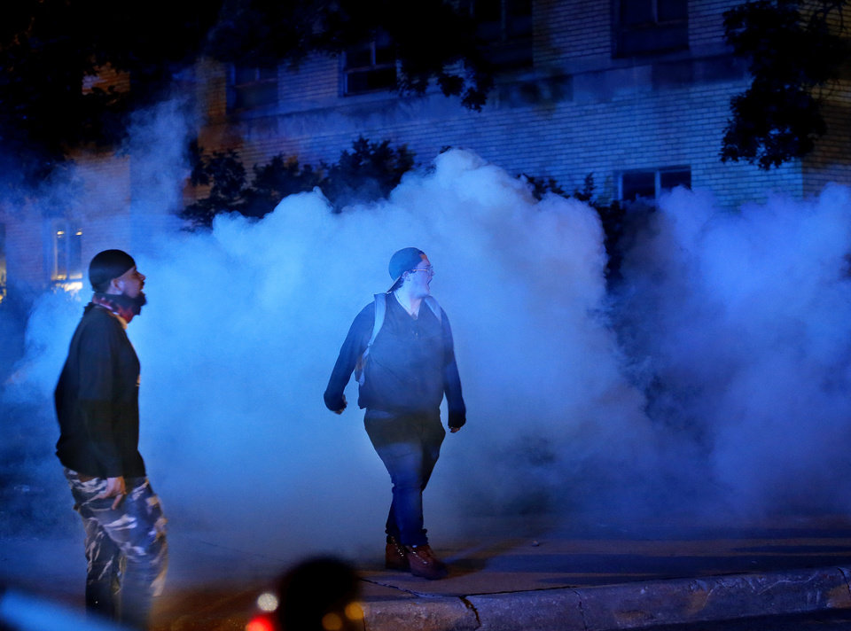 Photo - Protesters walk in a cloud of tear gas in front of the Oklahoma City Police Department in Oklahoma City, Saturday, May 30, 2020. The protest was in response to the death of George Floyd. [Sarah Phipps/The Oklahoman]