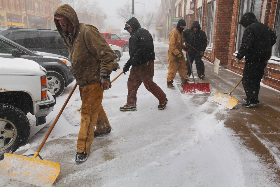 Photo - Employees with G.J. Holsworth & Sons shovel snow from the sidewalk  in Rapid City, S.D., Monday, March 31, 2014.  A spring snowstorm in the Upper Midwest on Monday shut down public schools, universities and government offices, made travel hazardous and life miserable for cattle ranchers in the midst of calving season. The National Weather Service issued blizzard warnings for much of the Dakotas and part of Minnesota, with the heaviest snow expected in eastern North Dakota and northwestern Minnesota.  (AP Photo/Rapid City Journal, Benjamin Brayfield)