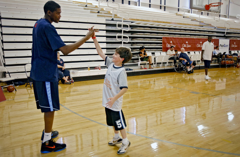 Photo - Kevin Durant, of the Oklahoma City Thunder, gives out high fives to camp participants during Durant's basketball camp at Heritage Hall on Tuesday, June 30, 2009, in Oklahoma City, Okla.  Photo by Chris Landsberger, The Oklahoman