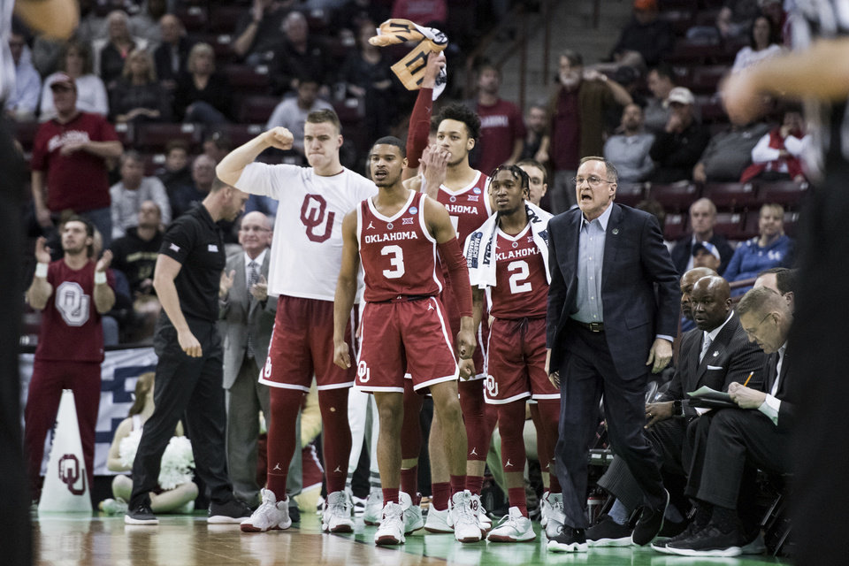Photo - Oklahoma head coach Lon Kruger, right, and his players react after a score against Mississippi during a first round men's college basketball game in the NCAA Tournament Friday, March 22, 2019, in Columbia, S.C. Oklahoma defeated Mississippi 95-72. (AP Photo/Sean Rayford)