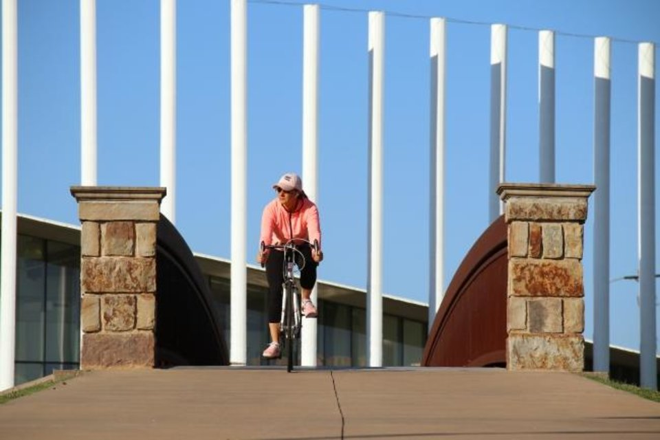 Photo -  A woman rides a bike along the Oklahoma River Trail near the Chesapeake Boathouse on Friday. [Doug Hoke/The Oklahoman]