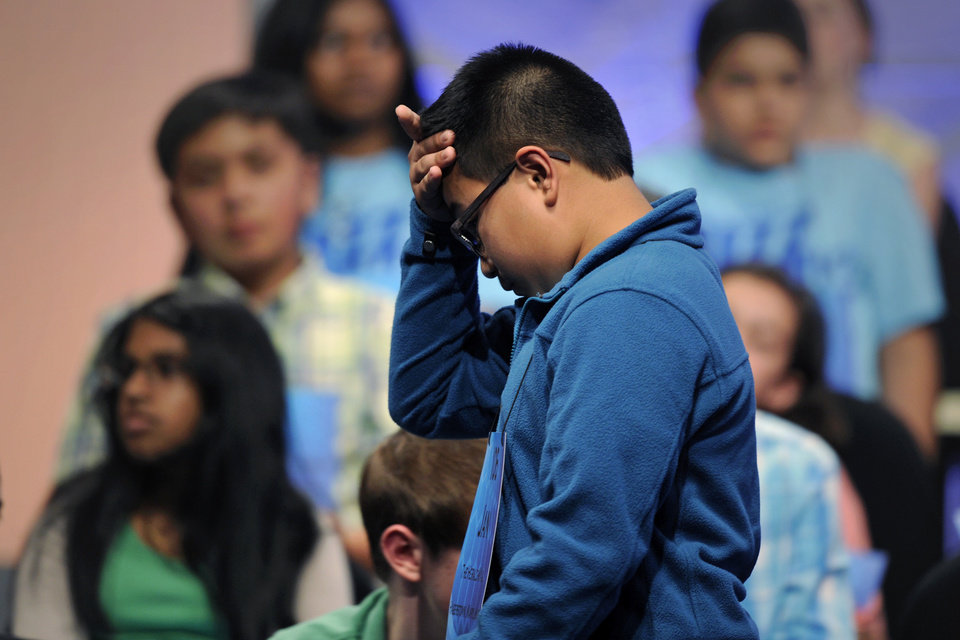 "Photo - Jan Lomahan, 13, of Hagerstown, Md., holds his forehead as he walks off-stage after missspelling the word ""adelie"" during the 2015 Scripps National Spelling Bee in Oxon Hill, Md., Wednesday, May 27, 2015. (AP Photo/Cliff Owen)"