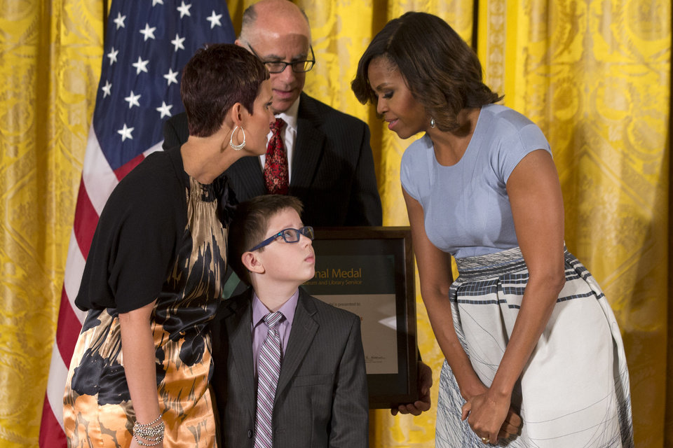 Photo - Spencer Hahn, 8, who had a stroke in-utero, looks up at first lady Michelle Obama while on stage with his mother Erica Hahn and The Children's Museum of Indianapolis President and CEO Jeffrey Patchen, as they accept a 2014 National Medal for Museum and Library Service during a ceremony in the East Room of the White House, Thursday, May 8, 2014, in Washington. The National Medal is the nation's highest honor given to museums and libraries for service to the community. (AP Photo/Jacquelyn Martin)