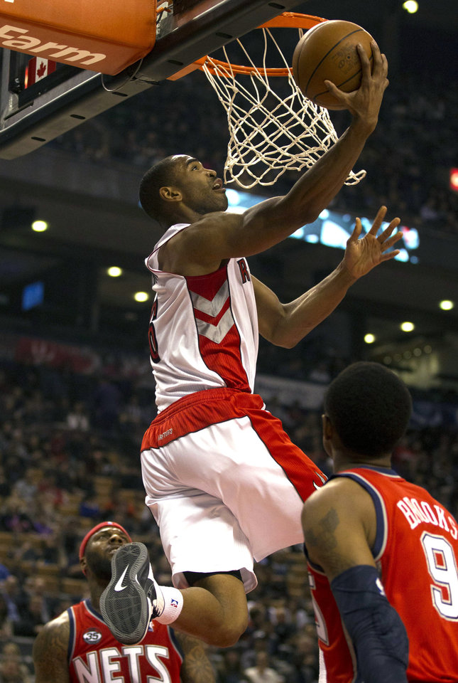 Photo -   Toronto Raptors' Alan Anderson, center, reverses to the hoop between New Jersey Nets defenders DeShawn Stevenson and MarShon Brooks, right, during the first half of an NBA basketball game in Toronto on Thursday, April 26, 2012. (AP Photo/The Canadian Press, Frank Gunn)