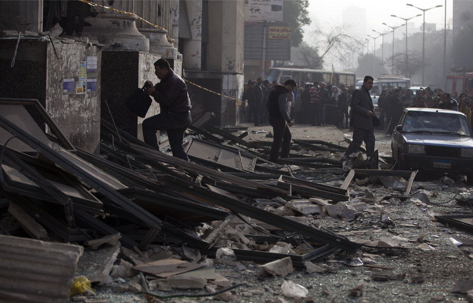 Photo - Egyptian police inspect the Imbaba courthouse after an early morning explosion damaged the building despite a massive security operation to protect polling stations and voters, in Cairo, Egypt, Tuesday, Jan. 14, 2014. The building was not a polling station and no one was reported injured in the blast.  Egyptians have started voting on a draft for their country's new constitution that represents a key milestone in a military-backed roadmap put in place after President Mohammed Morsi was overthrown in a popularly backed coup last July. (AP Photo/Khalil Hamra)