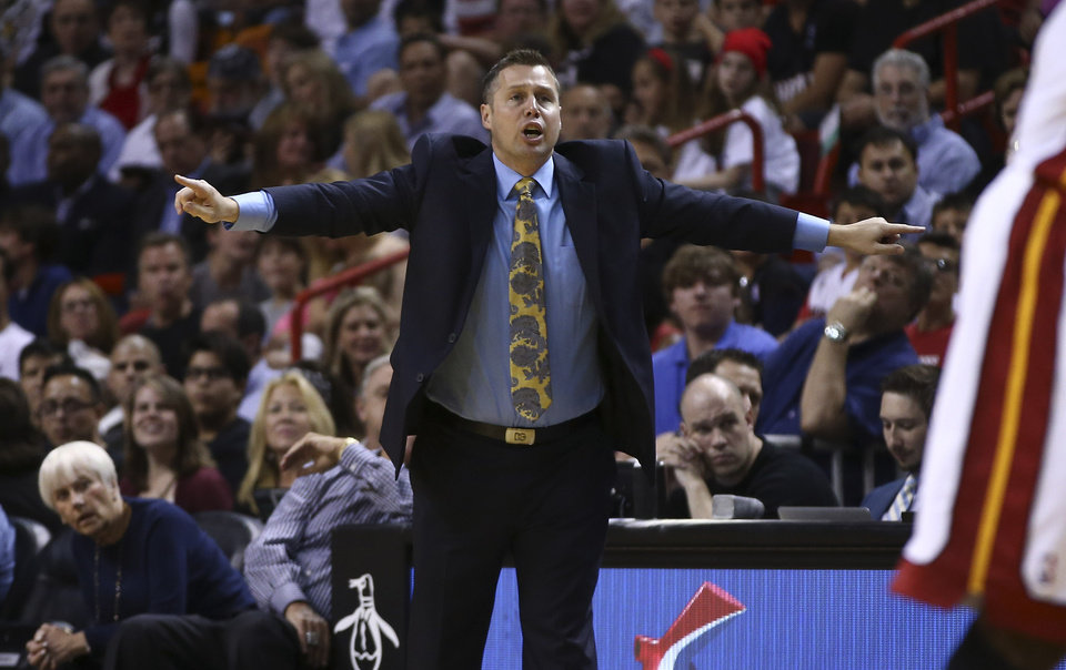 Photo - Memphis Grizzlies coach David Joerger yells instructions to his team during the first half of an NBA basketball game in Miami, Friday, March 21, 2014, against the Miami Heat. (AP Photo/J Pat Carter)