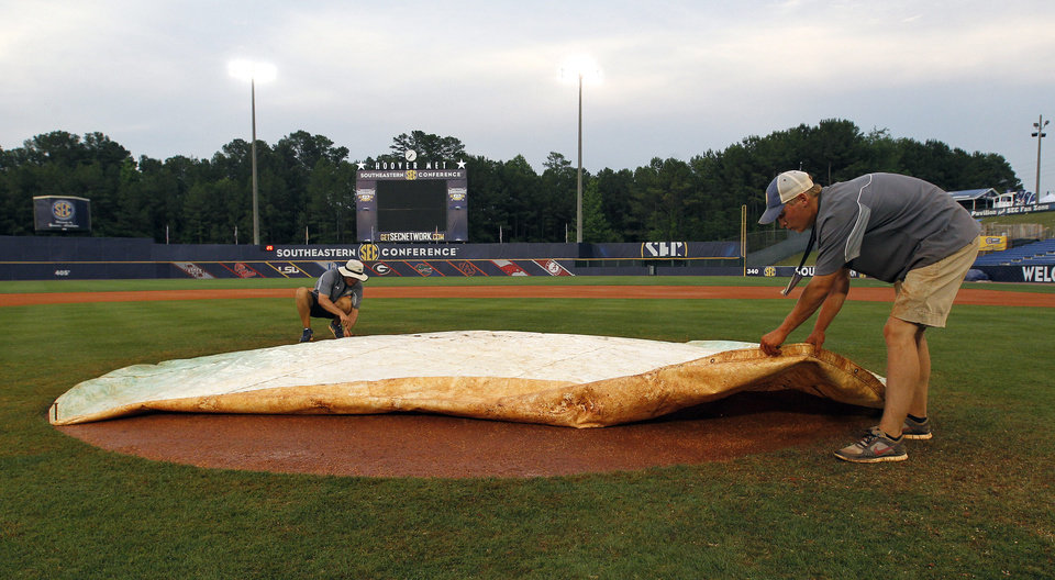 Photo - In this May 24, 2014 photo, John Wagnon, of Florida, and Justin Marlin, of Alabama, cover the pitcher's mound at the Southeastern Conference NCAA college baseball tournament in Hoover, Ala. A 40-man grounds crew labored to keep the Hoover Met's field in good shape for the the six-day, 17-game tournament. (AP Photo/Butch Dill)