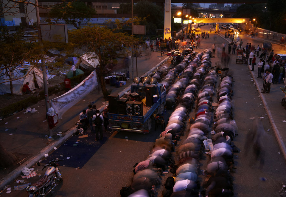 Photo -   In this Monday, April 30, 2012, photo, followers of Egyptian Muslim cleric and former candidate for Egyptian presidency, Hazem Salah Abu Ismail, pray at the location of their sit down on the road leading to the Defense Ministry, in Cairo, Egypt. (AP Photo/Fredrik Persson)