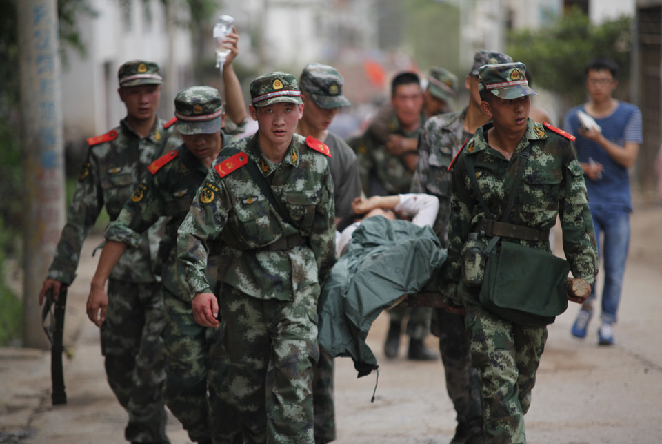 Photo - In this photo released by China's Xinhua News Agency, rescuers transport injured people after an earthquake in Zhaotong City in the densely populated Ludian county in southwest China's Yunnan Province, Sunday Aug. 3, 2014.  The strong earthquake in southern China's Yunnan province toppled thousands of homes on Sunday, killing at least 175 people and injuring more than 1,400, according to China's official Xinhua News Agency. (AP Photo / Xinhua, Zhang Guangyu) NO SALES