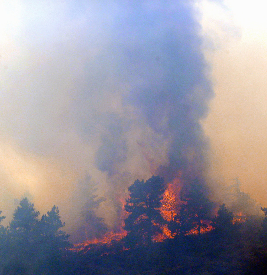 Photo - RETRANSMISSION TO CORRECT LOCATION - A wildfire burns out of control at Horsetooth Reservoir west of Fort Collins, Colo., on Friday, March 15, 2013. The 40-acre wildfire burning in gusty winds and warm weather was threatening homes west of Fort Collins on Friday and prompted about 50 people to leave the area. (AP Photo/Ed Andrieski)