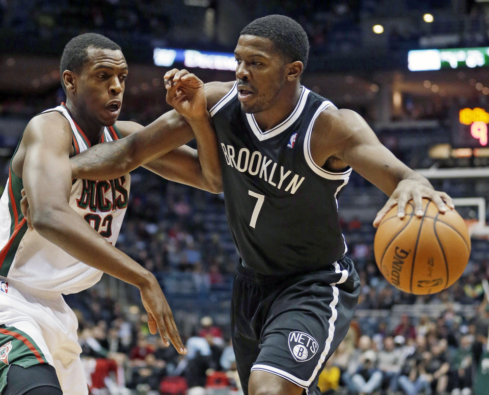 Photo - Brooklyn Nets' Joe Johnson tries to drive past Milwaukee Bucks' Khris Middleton during the first half of an NBA basketball game Saturday, Dec. 7, 2013, in Milwaukee. (AP Photo/Morry Gash)