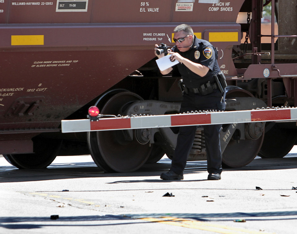 A BNSF officer investigates the scene of a pedestrian/train fatality at Boyd west of Classen on Saturday, Sept. 1, 2012 in Norman, Okla.  Photo by Steve Sisney, The Oklahoman