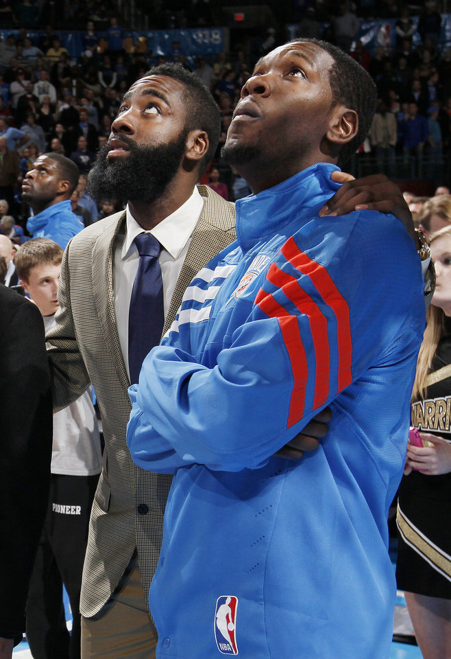 Photo - Oklaoma City's James Harden, left, and Royal Ivey watch the highiight video before the player introductions during an NBA basketball game between the Oklahoma City Thunder and the New Orleans Hornets at the Chesapeake Energy Arena in Oklahoma City, Monday, Feb. 20, 2012. Photo by Nate Billings, The Oklahoman