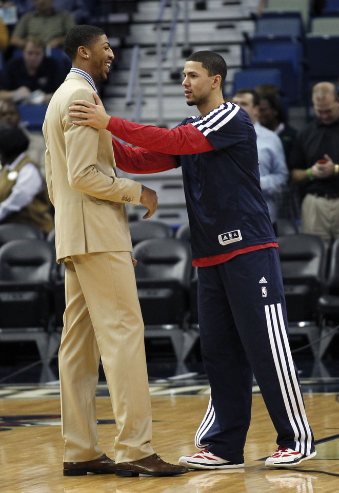 Photo - New Orleans Pelicans shooting guard Austin Rivers, right, laughs with power forward Anthony Davis before an NBA basketball game against the Dallas Mavericks in New Orleans, Wednesday, Dec. 4, 2013.  Davis is out for four to six weeks for a hand injury he sustained in a recent game against the Chicago Bulls. (AP Photo/Gerald Herbert)