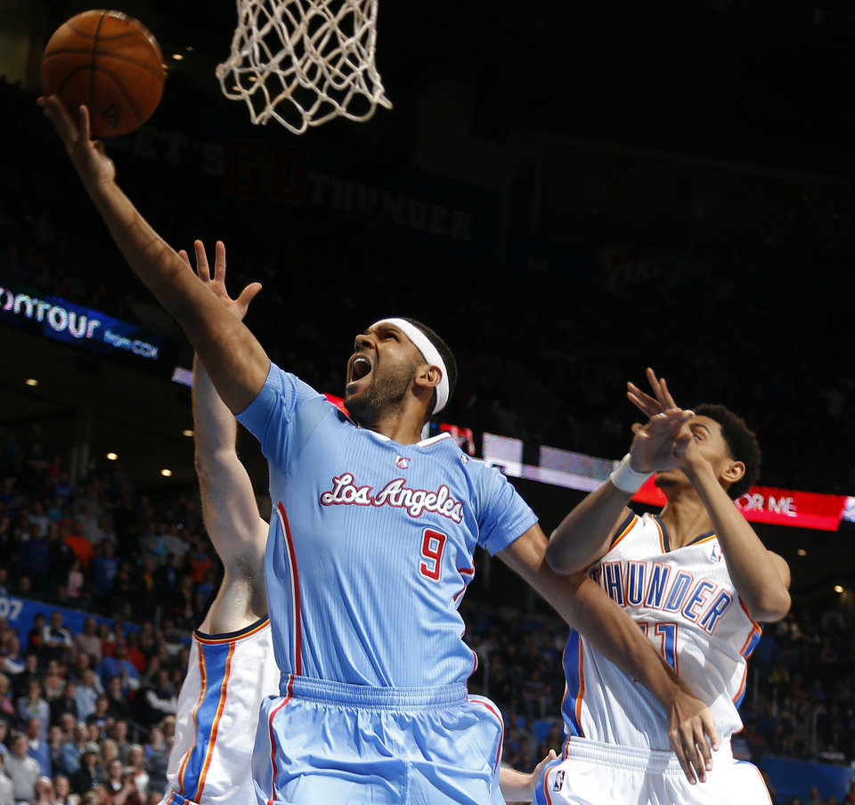 Photo - Los Angeles' Jared Dudley (9) shoots a lay up in front of Oklahoma City 's Jeremy Lamb (11) during the NBA game between the Oklahoma City Thunder and the Los  Angeles Clippers at the Chesapeake Energy Arena, Sunday, Feb. 23, 2014. Photo by Sarah Phipps, The Oklahoman