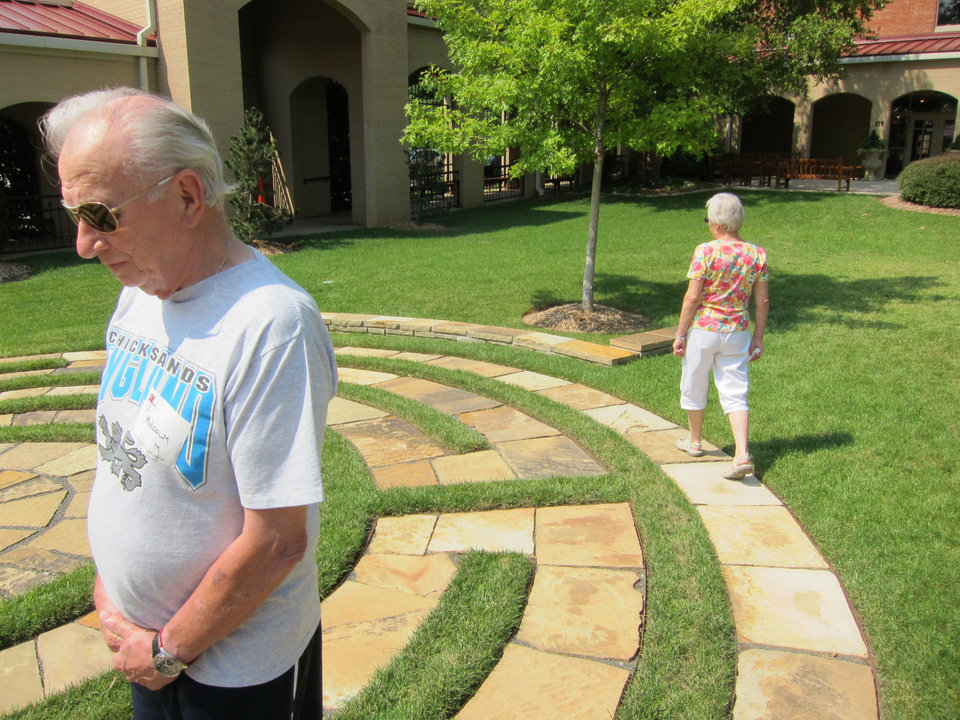 Photo - Malcolm and Kathy May, of Bethany, members of St. Paul's Episcopal Cathedral, walk the labyrinth in the church's east garden during