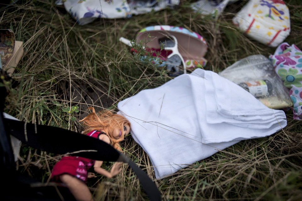 Photo - A doll and other personal effects lie on the ground at the crash site of a Malaysia Airlines jet near the village of Hrabove, eastern Ukraine, Saturday, July 19, 2014. World leaders demanded Friday that pro-Russia rebels who control the eastern Ukraine crash site of Malaysia Airlines Flight 17 give immediate, unfettered access to independent investigators to determine who shot down the plane. (AP Photo/Evgeniy Maloletka)