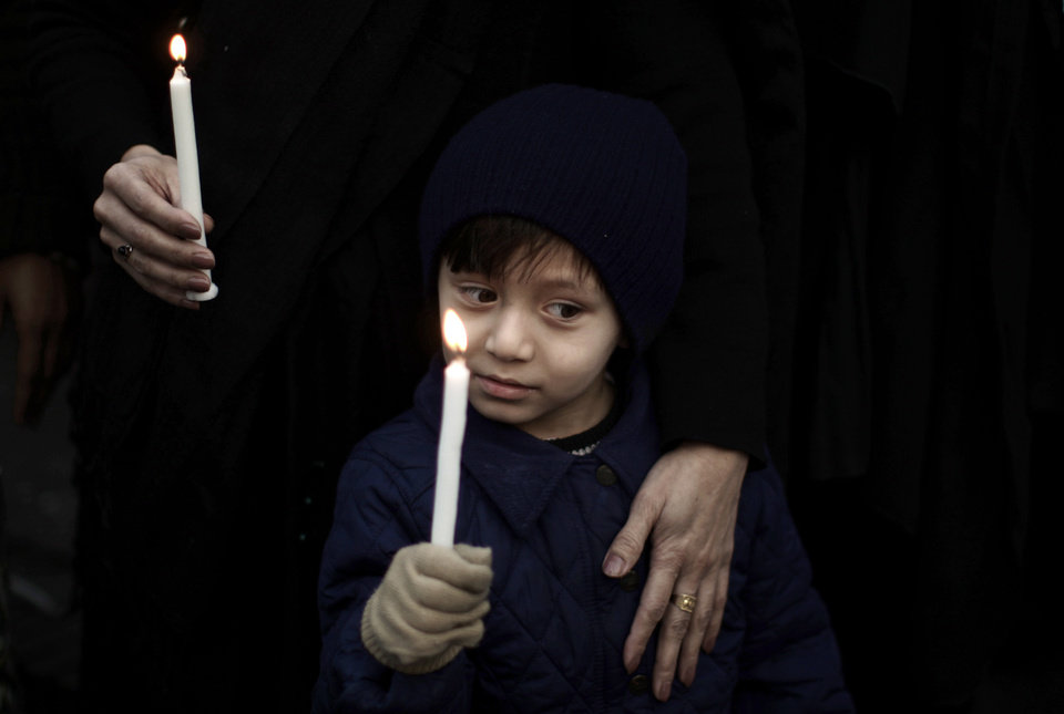 A Pakistani boy holds a candle while he and his mother take part in a protest to condemn Thursday's deadly bombings in Quetta, in Islamabad, Pakistan, Friday, Jan. 11, 2013. Shiites in a southwestern Pakistani city hit by a brutal terror attack refused to bury their dead Friday in protest, demanding that the government do something to protect them from what has become a barrage of bombings and shootings against the minority Muslim sect. (AP Photo/Muhammed Muheisen)