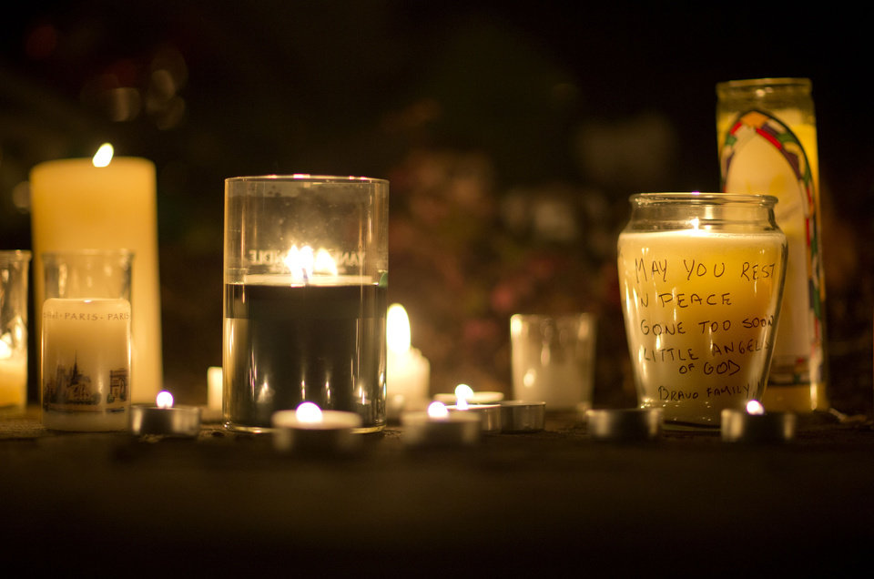 Photo - A message is seen on a candle outside the St. Rose of Lima Roman Catholic Church, Saturday, Dec. 15, 2012, in Newtown, Conn. A man killed his mother at their home and then opened fire Friday inside the Sandy Hook Elementary school, massacring 26 people, including 20 children, as youngsters cowered in fear to the sound of gunshots reverberating through the building and screams echoing over the intercom. (AP Photo/David Goldman) ORG XMIT: CTDG112
