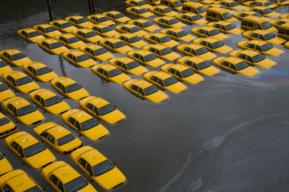 Photo - FILE - In this Oct. 30, 2012 file photo, a parking lot full of yellow cabs in Hoboken, N.J.  is flooded as a result of Superstorm Sandy. Global warming is rapidly turning America the beautiful into America the stormy, sneezy and dangerous, according to the National Climate Assessment report released Tuesday, May 6, 2014. (AP Photo/Charles Sykes, File)