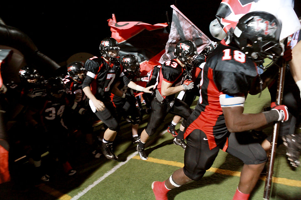 Westmoore's Trevor Thompson (7) and Cody Feuerborn (43) join their teammates as they take the field before their playoff game against Owasso at Moore High School in Moore, Oklahoma, on Friday Nov. 19, 2010. Photo by John Clanton, The Oklahoman