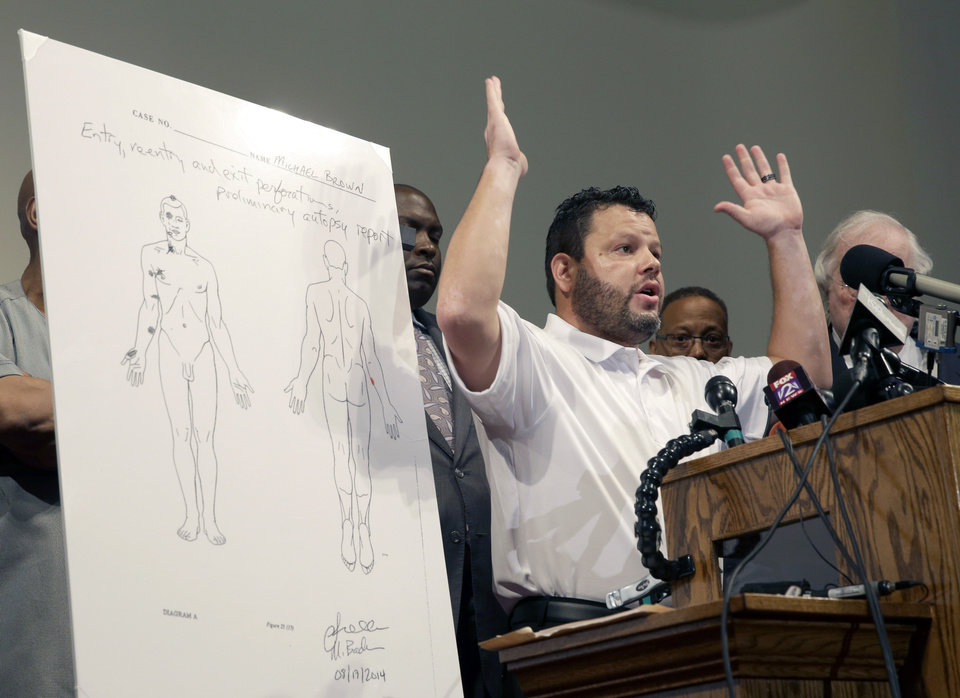 Photo - Forensic pathologist Shawn Parcells speaks during a news conference to share preliminary results of a second autopsy done on Michael Brown Monday, Aug. 18, 2014, in St. Louis County, Mo. The independent autopsy shows 18-year-old Michael Brown was shot at least six times, and Parcells, who assisted former New York City chief medical examiner Dr. Michael Baden during the autopsy, said a graze wound on Brown's right arm could have occurred in several ways. (AP Photo/Jeff Roberson)