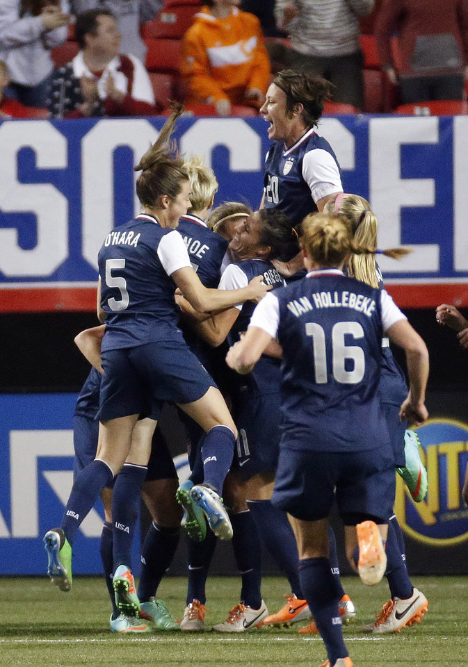 Photo - U.S. players, including Abby Wambach (20) and Kelly O'Hara (5) celebrate a goal during the first half of an exhibition soccer match against Russia on Thursday, Feb. 13, 2014, in Atlanta. (AP Photo/John Bazemore)