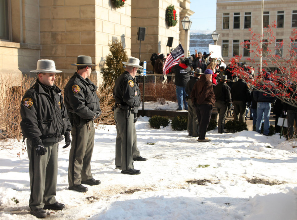 Photo - Jefferson Co. sheriff's deputies stand nearby during the  protest at the Jefferson County Courthouse in Steubenville, Ohio, Saturday, Jan. 5, 2013. Authorities investigating rape accusations against two high school football players in eastern Ohio launched a website Saturday as interest in the case balloons, an extraordinary step designed to combat the misperception