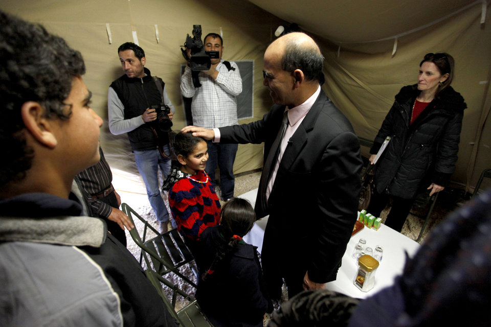 Kader Arif, French Minister for Veteran affairs, middle, meets with Syrian refugee families in the French military mobile hospital, at Zaatari Syrian refugee camp, near the Syrian border in Mafraq, Jordan, Tuesday, Dec. 25, 2012. (AP Photo/Mohammad Hannon)