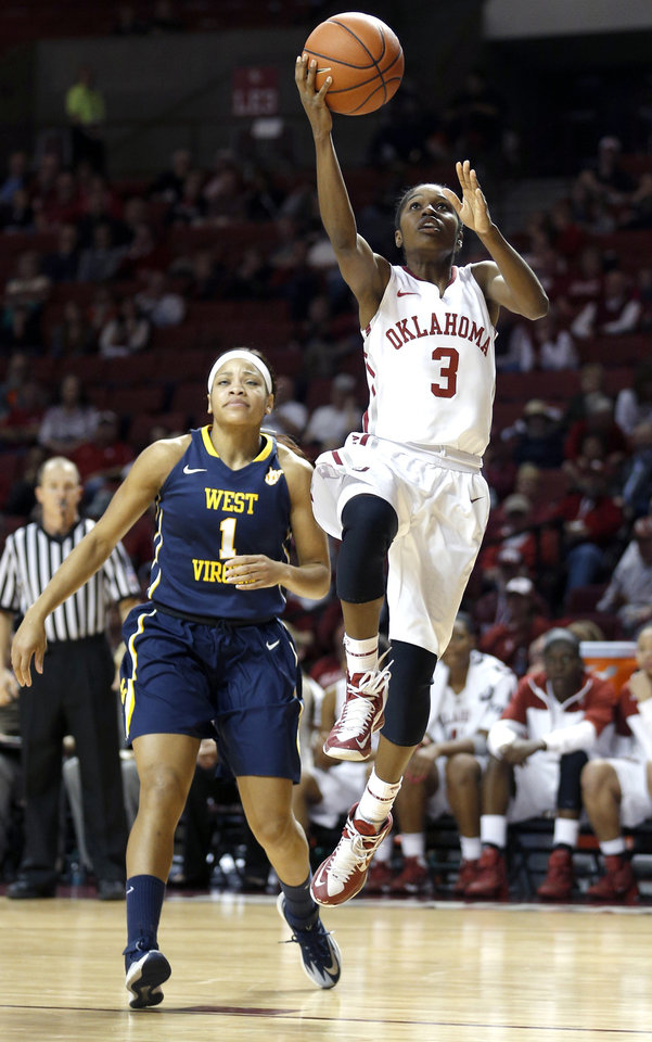 Photo - Oklahoma Aaryn Ellenberg (3) shoots a lay up in front of West Virginia Christal Caldwell (1)during the women's basketball game between, University of Oklahoma and West Virginia, Thursday, Feb. 13, 2014, in Norman, Okla. Photo by Sarah Phipps, The Oklahoman