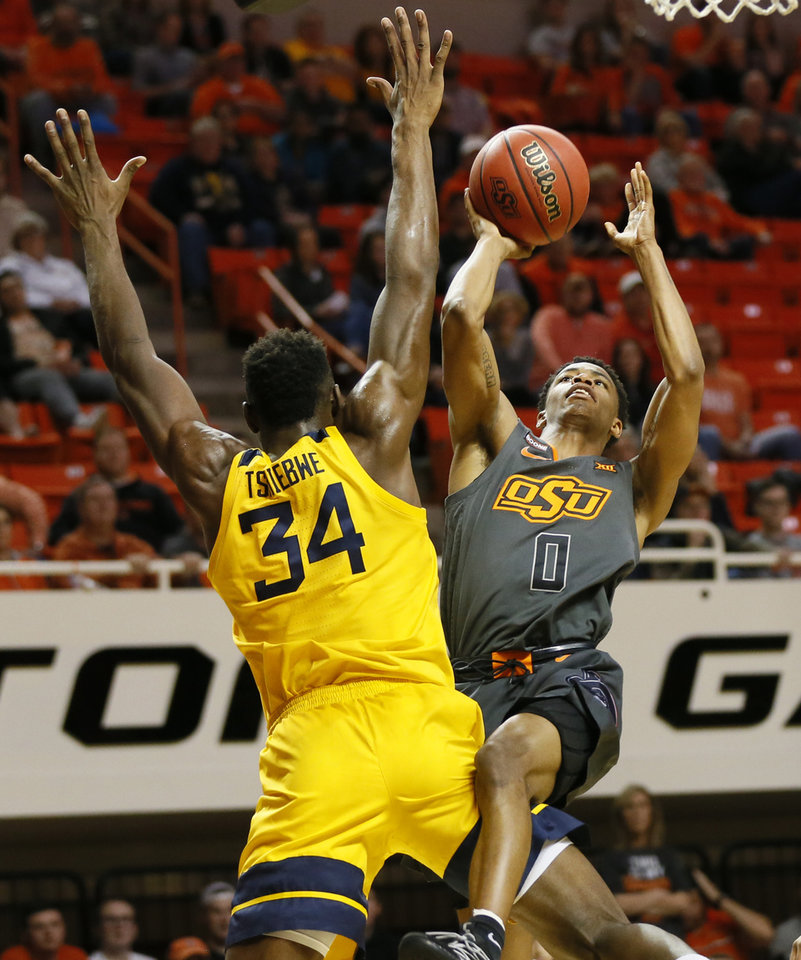 Photo - Oklahoma State's Avery Anderson III (0) shoots against West Virginia's Oscar Tshiebwe (34) in the first half during a men's college basketball game between the Oklahoma State Cowboys and West Virginia Mountaineers at Gallagher-Iba Arena in Stillwater, Okla., Monday, Jan. 6, 2020. [Nate Billings/The Oklahoman]