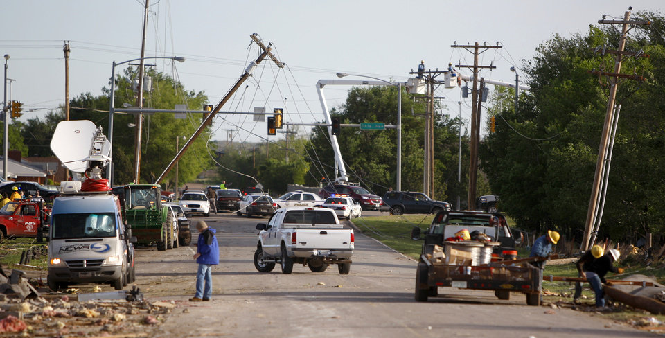 Photo - Utility lines hang over a street in Woodward, Okla., Sunday, April 15, 2012. A tornado that killed five people struck Woodward, Okla., shortly after midnight on Sunday, April 15, 2012.  Photo by Bryan Terry, The Oklahoman