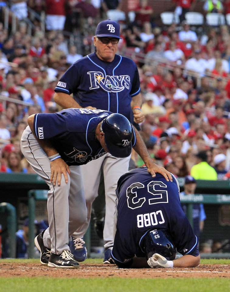 Photo - Tampa Bay Rays' Alex Cobb (53) is checked on by third base coach Tom Foley and manager Joe Maddon, top, after being hit on the right arm by a pitch during the fourth inning of a baseball game against the St. Louis Cardinals, Wednesday, July 23, 2014, in St. Louis. Cobb was able to stay in the game. (AP Photo/Jeff Roberson)