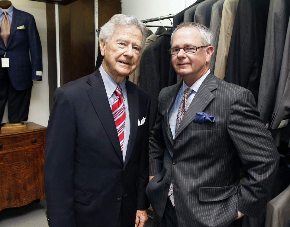 Photo - Hoot Gibson, who founded McCall's men's store in downtown Edmond 60 years ago, stands in the store with his son, Steve, who is now the owner. Hoot Gibson still works in the store each week.