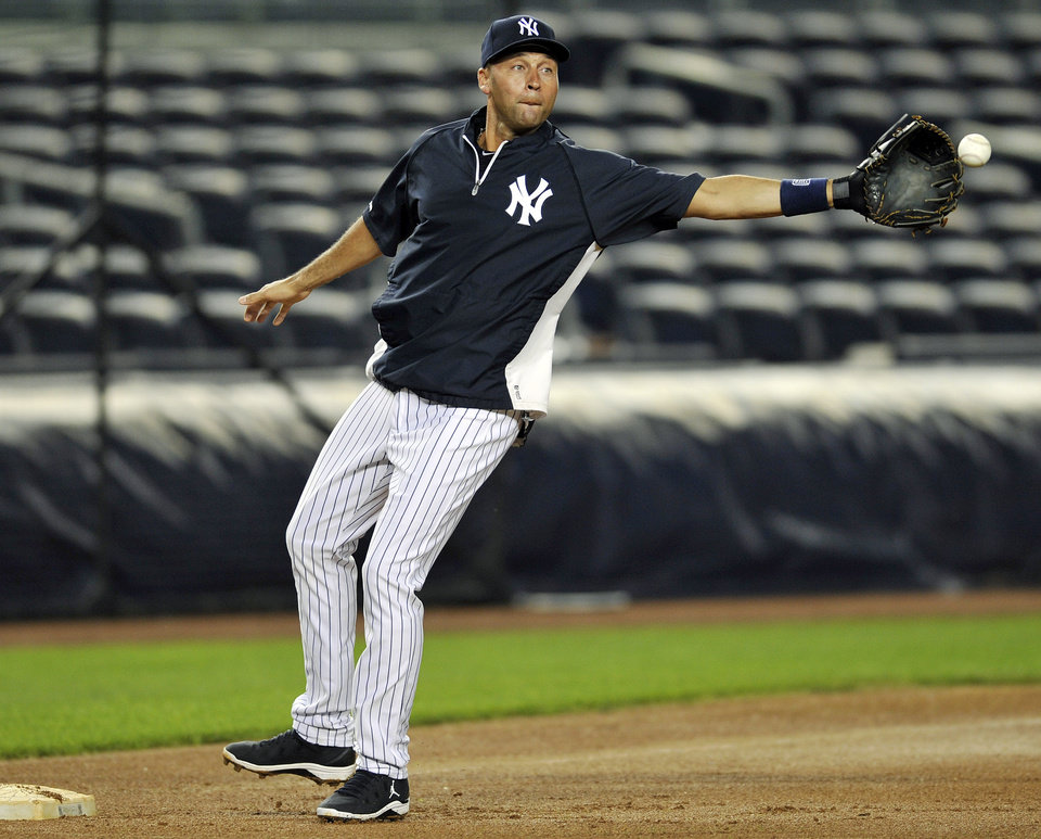 Photo -   New York Yankees shortstop Derek Jeter reaches for a ball as he covers third base during baseball practice Friday, Oct. 5, 2012, at Yankee Stadium in New York for an American League division series. (AP Photo/Bill Kostroun)