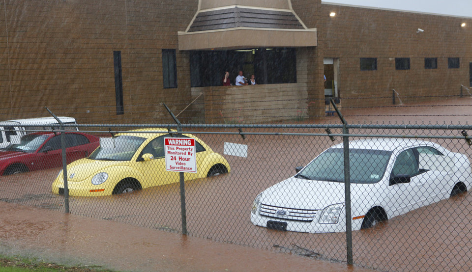 Photo - Employees at the Braums corporate office, I-35 and 63rd, look out at the flooded parking lot Monday,  June 14, 2010.    Photo by David McDaniel, The Oklahoman