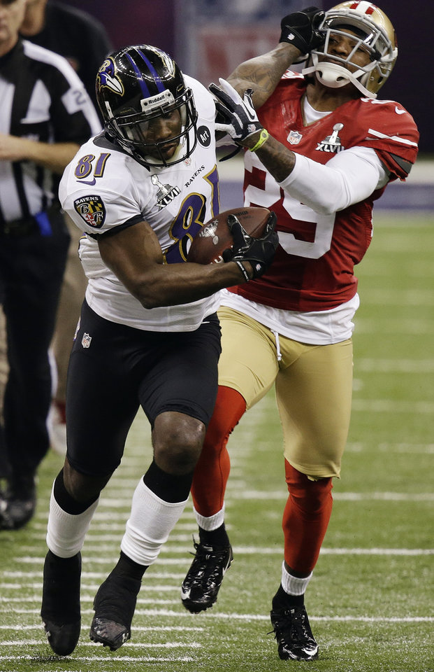 Photo - FILE - In this Feb. 3, 2013, file photo, Baltimore Ravens wide receiver Anquan Boldin (81) stiff-arms San Francisco 49ers cornerback Chris Culliver (29) during the second half of the NFL Super Bowl XLVII football game in New Orleans. The Ravens announced on Monday, March 11, that the 49ers have acquired Boldin for a sixth-round draft pick. (AP Photo/Gene Puskar, File)