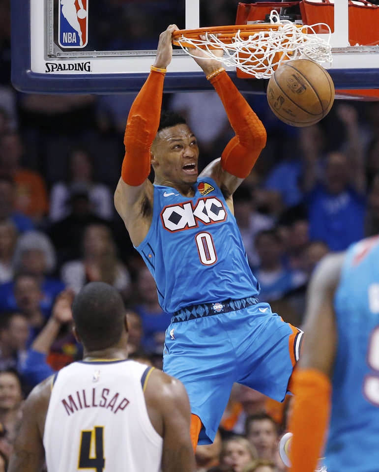 Photo - Oklahoma City Thunder guard Russell Westbrook (0) dunks in front of Denver Nuggets forward Paul Millsap (4) in the first half of an NBA basketball game Friday, March 29, 2019, in Oklahoma City. (AP Photo/Sue Ogrocki)