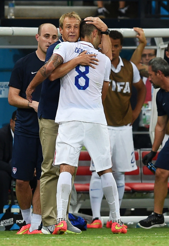 Photo - United States' head coach Juergen Klinsmann hugs United States' Clint Dempsey as Dempsey is substituted during the group G World Cup soccer match between the USA and Portugal at the Arena da Amazonia in Manaus, Brazil, Sunday, June 22, 2014. (AP Photo/Paulo Duarte)