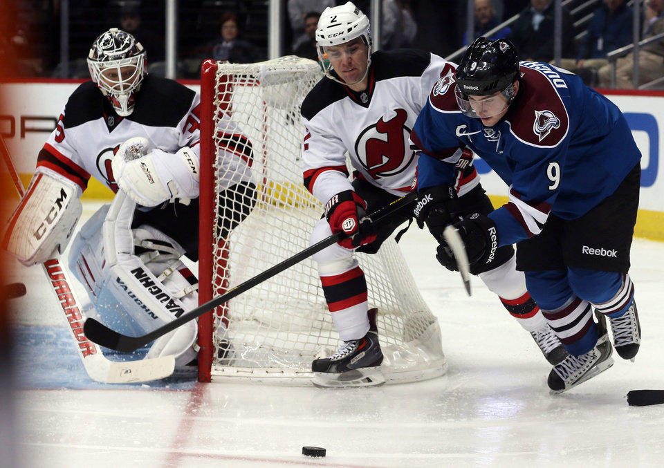 Photo - Colorado Avalanche center Matt Duchene, right, pursues the puck with New Jersey Devils defenseman Marek Zidlicky, center, of the Czech Republic, as Devils goalie Cory Schneider covers the net in the second period of an NHL hockey game in Denver, Thursday, Jan. 16, 2014. (AP Photo/David Zalubowski)