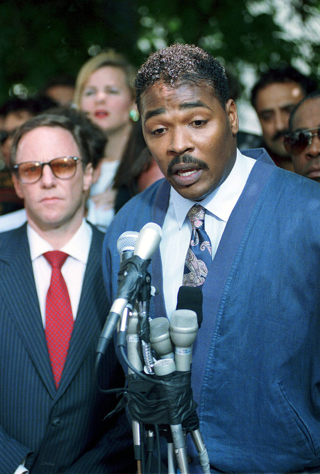 Photo -   FILE-In this May 1,1992 file photo Rodney King, right, makes his first statement, pleading for an end to the rioting in South Central Los Angeles, in Los Angeles. At left is King's attorney Steven Lerman. On April 29, 1992, four white police officers were declared innocent in the beating of black motorist Rodney King, and Los Angeles erupted in the deadliest riots of the century. (AP Photo/David Longstreath,File)