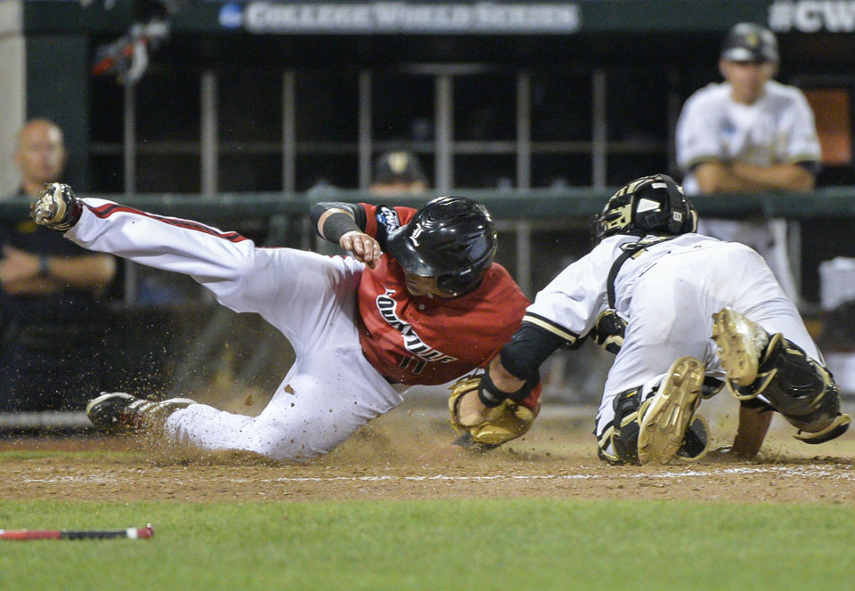 Photo - Louisville's Zach Lucas, left, slides home past Vanderbilt catcher Karl Ellison on a single by Nick Solak in the seventh inning of an NCAA baseball College World Series game in Omaha, Neb., Saturday, June 14, 2014. (AP Photo/Ted Kirk)