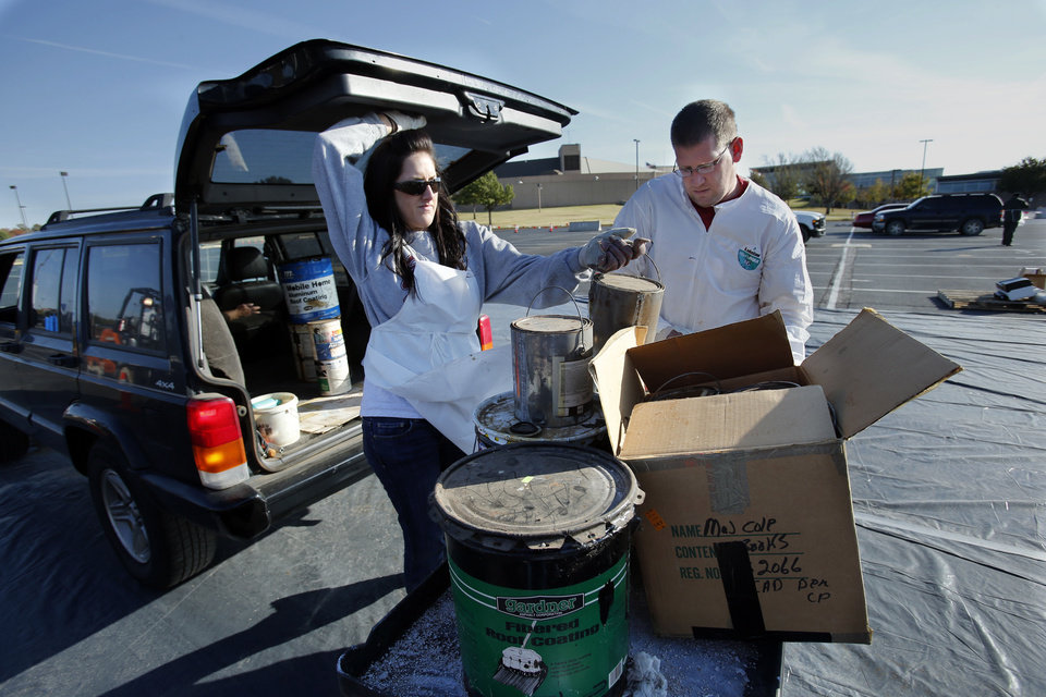 Sarah Gulledge and Chris Gwin unload cans of paint from a Norman resident�s car Saturday during a city-sponsored household hazardous waste event. PHOTOS BY STEVE SISNEY, THE OKLAHOMAN