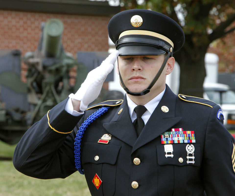 Photo - Above: Staff Sgt. Therin Miller, of the Governor's Honor Guard, salutes during a wreath presentation at the annual Veteran's Day ceremony at the 45th Infantry Museum in Oklahoma City.