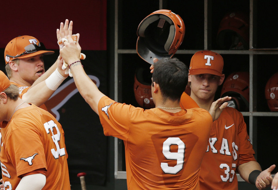 Photo - Texas' C.J. Hinojosa (9) gets high-fives in the dugout from his teammates after scoring in the second inning of a semifinal against Oklahoma State in the Big 12 NCAA college baseball tournament in Oklahoma City, Saturday, May 24, 2014. AP Photo/Sue Ogrocki)