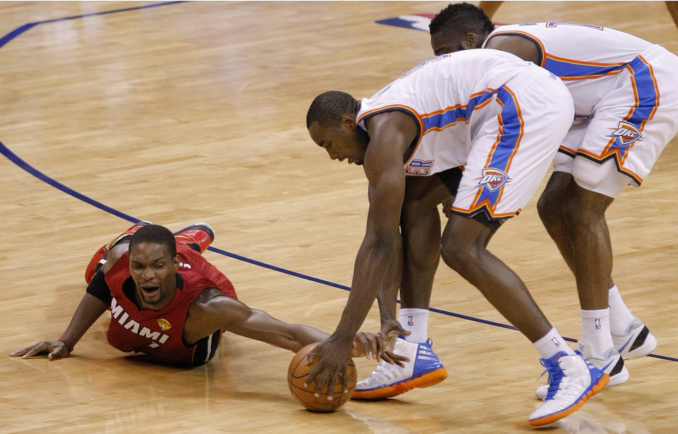 NBA BASKETBALL: Miami\'s Chris Bosh (1) dives for the ball beside Oklahoma City\'s Serge Ibaka, center, and Oklahoma City\'s James Harden during Game 1 of the NBA Finals between the Oklahoma City Thunder and the Miami Heat at Chesapeake Energy Arena in Oklahoma City, Tuesday, June 12, 2012. Photo by Sarah Phipps, The Oklahoman