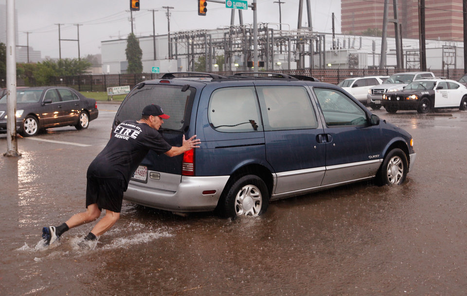 Photo - An Oklahoma City firefighter pushes a van that had stalled in high water on Classen Blvd, just west of the downtown area. Torrential rain caused flooding in Oklahoma City, Monday, June 14, 2010.     by Jim Beckel, The Oklahoman