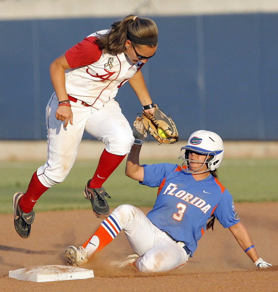 Photo - Alabama's Kaila Hunt (10) leaps over second base as Florida's Aja Paculba (3) slides during the Women's College World Series game between Florida and Alabama at the ASA Hall of Fame Stadium in Oklahoma City, Sunday, June 5, 2011. Photo by Garett Fisbeck, The Oklahoman